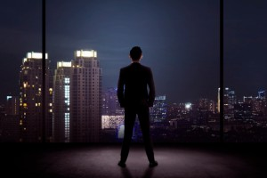 Man standing in his office looking at the city